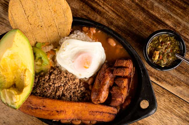Bandeja Paisa is the typical dish of the Paisa culture, which is composed by eggs, avocado, beans, salad, meat and tortitas.